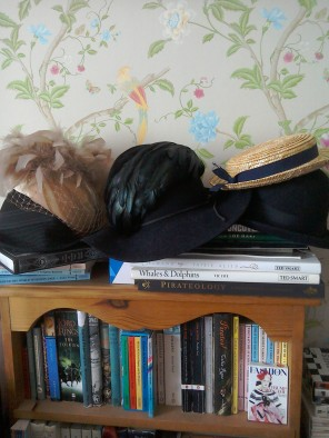 Vintage hats piled up on bookshelf-straw tilt boater by The Girl loves vintage-Laura Ashley Summer Palace wallpaper