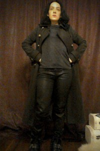 The Bridge Saga Khaki Next military style coat, dark top, wax coated black trousers and leather biker boots
